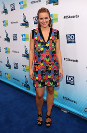 Kristen Bell pulled her look together, pairing solid black strappy sandals with a wildy printed shift.
