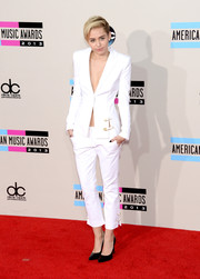 Miley Cyrus jumped in on the sexy pantsuit trend with this white number during the American Music Awards.