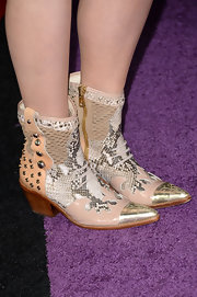 Opting for a totally cowgirl-inspired red carpet look, RaeLynn chose these gray, tan, and gold studded cowboy boots.