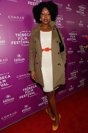 Amanda Warren paired a classic trenchcoat over her white cocktail dress for a preppy and sophisticated look.