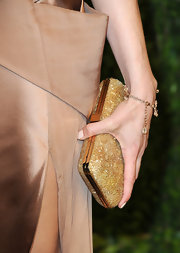 Aubrey Plaza accessorized with an elegant gold hard-case clutch at the Vanity Fair Oscar party.