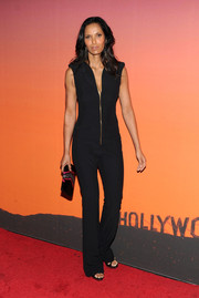 Padma Lakshmi complemented her jumpsuit with a black envelope clutch with silver and pink detailing.