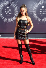 """""""Break Free"""" singer Ariana Grande went for an uncharacteristically edgy look wearing a short Moschino dress and Tom Ford shoes. leather dress and over-the-knee boots."""