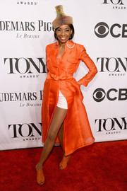Adriane Lenox layered an orange evening coat over white shorts for a unique Tony Awards red carpet look.