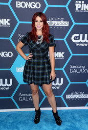 Jillian Rose Reed contrasted her girly dress with edgy black ankle boots featuring buckle and strap accents.
