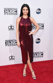 Selena Gomez brought major shimmer to the American Music Awards red carpet with this fully sequined red halter dress by Givenchy.