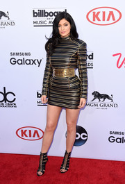 Kylie Jenner was a tough beauty at the Billboard Music Awards in a black and gold striped leather dress by Balmain, tightly cinched in at the waist with an oversized metallic belt.
