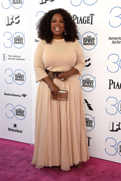 Oprah Winfrey topped off her ensemble with a shiny gold box clutch.