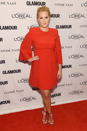 Amy Schumer opted for a classic red Alexander McQueen cocktail dress with bell sleeves for her Glamour Women of the Year Awards look.