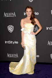 Camilla Luddington went for classic glamour at the InStyle and Warner Bros. Golden Globes party in a Gustavo Cadile strapless gown featuring lovely yellow embroidery on an ivory background.