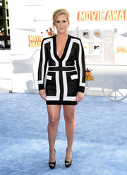 Amy Schumer put on a bold display of cleavage and legs in a black-and-white Balmain mini dress during the MTV Movie Awards.