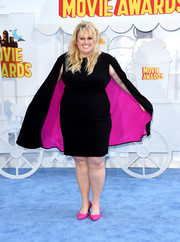 Rebel Wilson looked striking in a little black dress with a hot pink-lined cape at the MTV Movie Awards.