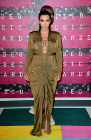Kim Kardashian wrapped up her pregnancy curves in an olive-green lace-up maxi dress by Balmain for the MTV VMAs.