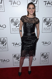 Kristen Stewart matched her knee-length black and lace skirt to her top to complete her sleek outfit.
