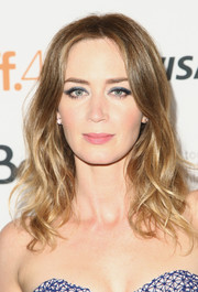 Emily Blunt accentuated her eyes with a heavy application of blue-gray shadow on the top lids.