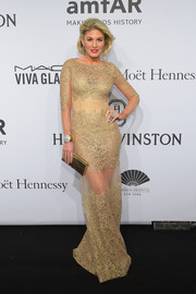Hofit Golan completed her high-shine look with a metallic gold clutch.