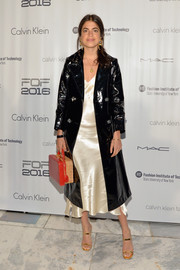 Leandra Medine arrived for the 2016 Future of Fashion runway show wearing a cool black patent coat over a white satin dress.