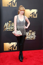 Ashley Rickards added more shine with a metallic gold clutch.