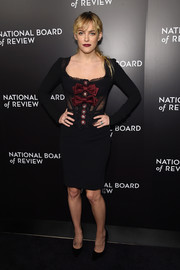 Riley Keough sizzled at the National Board of Review Gala in a black Dolce & Gabbana corset dress with a sheer midsection and red bow detailing.