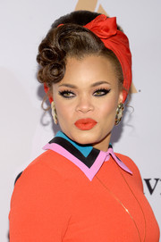 Andra Day accentuated her pout with bright orange lippy.