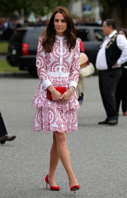 Kate Middleton tied her perfectly coordinated look together with a red suede clutch by Miu Miu.