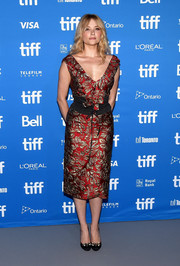 Haley Bennett chose a red and silver brocade dress by Prada for 'The Magnificent Seven' press conference.