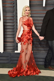 Gwen Stefani put on a sultry display in a sheer red gown by Yanina Couture during the Vanity Fair Oscar party.