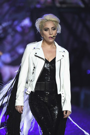Lady Gaga was edgy-sexy in a white leather moto jacket layered over a sequined catsuit while performing at the Victoria's Secret fashion show.