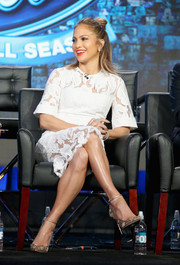 Jennifer Lopez paired embellished gold ankle-strap pumps by Jimmy Choo with a lacy white dress for the Winter TCA Tour.
