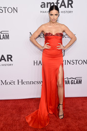 Adriana Lima ravished in a strapless red Marchesa gown with an embellished sweetheart neckline and a thigh-high slit at the amfAR New York Gala.