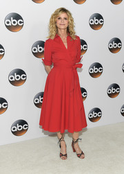 Kyra Sedgwick complemented her chic dress with red and black ankle-tie sandals.