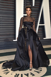 Janelle Monae went for edgy glamour in a black Alexandre Vauthier Couture gown, featuring a fishnet yoke and sleeves, a voluminous skirt, and a grommeted belt, at the Vanity Fair Oscar party.