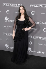 Kat Dennings kept it low-key in a black gown with sheer sleeves at the 2018 Baby2Baby Gala.