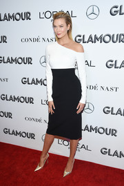 Karlie Kloss styled her dress with pointy gold pumps.