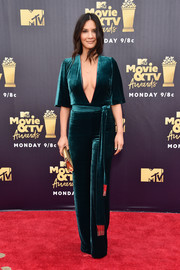 Olivia Munn took a sexy plunge with this teal velvet jumpsuit by Galvan at the 2018 MTV Movie & TV Awards.