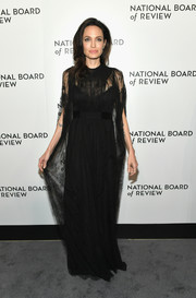 Angelina Jolie looked supremely elegant in a caped black lace gown by Valentino at the 2018 National Board of Review Awards Gala.