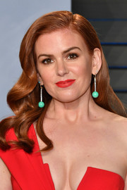 Isla Fisher contrasted her red outfit with dangling green spheres by Irene Neuwirth.