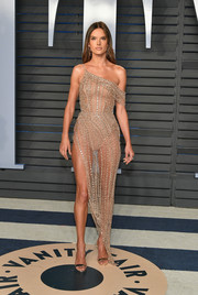 Alessandra Ambrosio brought a high dose of sex appeal to the 2018 Vanity Fair Oscar party with this sheer, asymmetrical nude dress by Ralph & Russo Couture.
