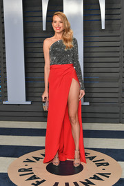 Petra Nemcova looked fab in a Redemption Couture one-shoulder gown, featuring a glittery gunmetal bodice and a high-slit red skirt, at the 2018 Vanity Fair Oscar party.