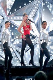 Dua Lipa teamed black tights with a strappy red bodysuit for her performance at the 2019 American Music Awards.