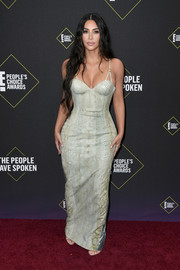 Kim Kardashian hit the 2019 E! People's Choice Awards wearing a curve-hugging sage-green snakeskin gown by Versace.
