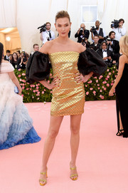 Karlie Kloss looked fab in a gold Gucci x Dapper Dan mini dress with contrast off-the-shoulder puffed sleeves at the 2019 Met Gala.
