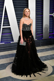 Halston Sage paired her dress with a sparkling box clutch by Edie Parker.