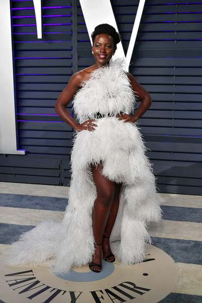 Lupita Nyong'o stole the spotlight in a feathered one-shoulder dress by Oscar de la Renta at the 2019 Vanity Fair Oscar party.