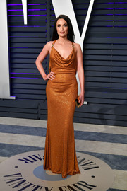 Kacey Musgraves looked sultry in a draped rust-colored halter gown by Versace at the 2019 Vanity Fair Oscar party.