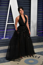 Priyanka Chopra went for edgy elegance in an embellished black halter gown by Elie Saab Couture at the 2019 Vanity Fair Oscar party.