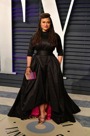 A pair of gold mules with red straps finished off Ava DuVernay's outfit.