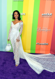 Serayah McNeill gave us bridal vibes with this off-the-shoulder white lace jumpsuit by Pamella Roland at the 2019 amfAR Gala Los Angeles.