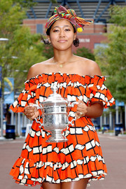 Naomi Osaka looked cheery in an off-the-shoulder orange print dress while showing off her U.S. Open trophy.