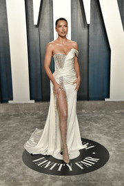 Adriana Lima looked mesmerizing in a high-slit, off-one-shoulder ivory gown by Ralph & Russo Couture at the 2020 Vanity Fair Oscar party.